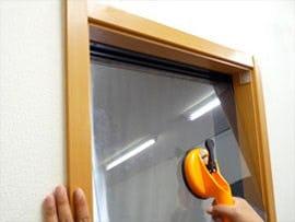 ガラス吸盤を使って窓枠にガラス板をはめ込む様子 -1